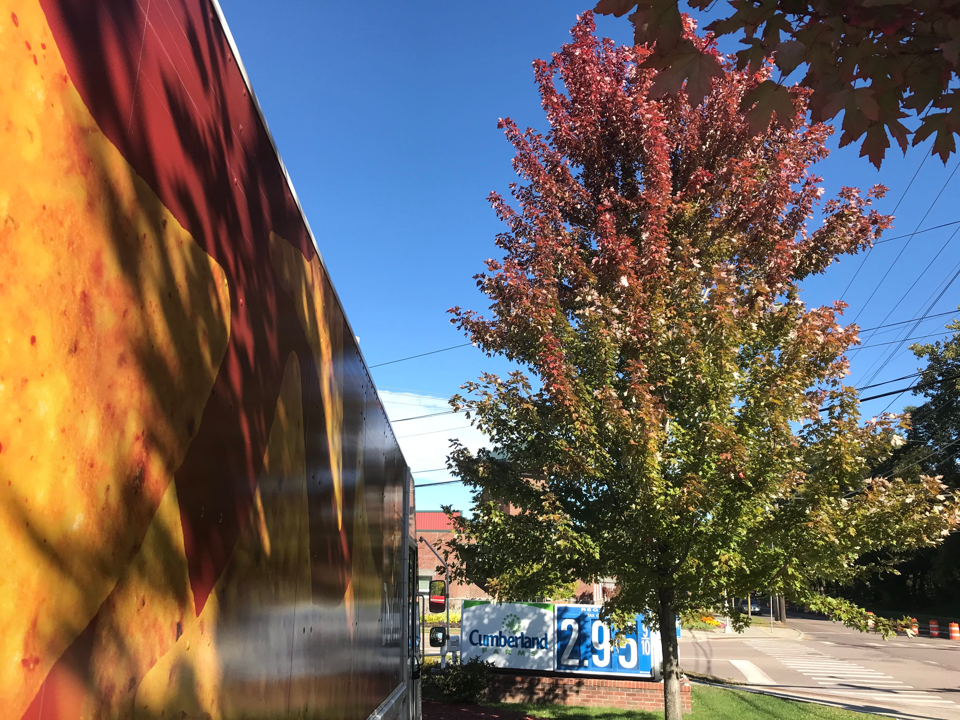 A maple tree turns deep red, crown-first, next to snack-food delivery truck at Cumberland Farms at Pine Street and Lakeside Avenue in Burlington on Friday, Oct. 5, 2018