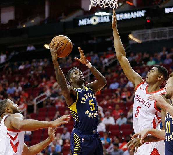 Edmond Sumner #5 of the Indiana Pacers drives between Bruno Caboclo #5 of the Houston Rockets and Eric Gordon #10 to the basket in the fourth quarter at Toyota Center on October 4, 2018 in Houston, Texas.