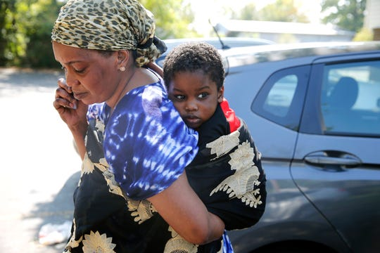 Aissata Aly, of Lockland, talks on the phone to her husband, Amadou Sow, who is in custody in a Morrow County prison, as she holds her son Muhammad, 3.