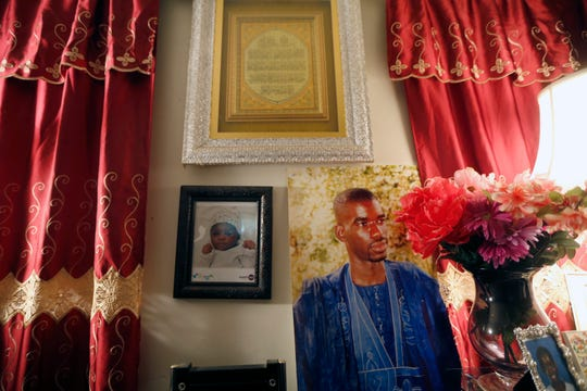 A photo of Amadou Sow, right, hangs next to his youngest child's photo at his Lockland home Friday, October 5, 2018. Sow born in Mauritania but has lived in the U.S. for 30 years was taken into custody by ICE in August. Sow worked at a manufacturing company for 20 years in Lebanon, is in danger of being deported back to Mauritania. The United Nations says Mauritania that Muslim and ethnic black minority men are being trafficked into slavery and sold in Libya.