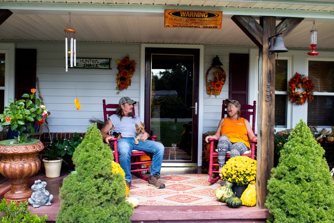 Tim and Ellen Bakos sit on their porch at their home with their dog Sonny after the capture of Kirby Wallace nearby the Montgomery and Stewart County line Friday, Oct. 5, 2018, in Tenn.