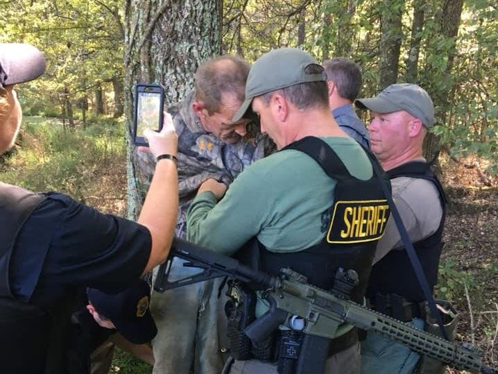 Henry County Sheriff Monte Belew, center, and Henry County Sheriff's Cpl. Stacey Bostwick, far right, take accused killer Kirby Wallace into custody Friday morning.