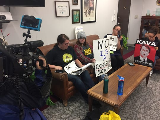 From left, Heather Pearson of Logan, Emma Schmit of Rockwell City and Jess Mazour of Des Moines sit in Sen. Chuck Grassley's office Friday, Oct. 5, 2018, to protest the Supreme Court nomination of Brett Kavanaugh.