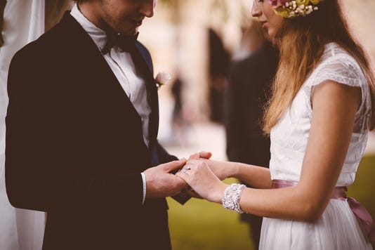 Newlywed Couple With Wedding Rings Holding Hands At Wedding Ceremony