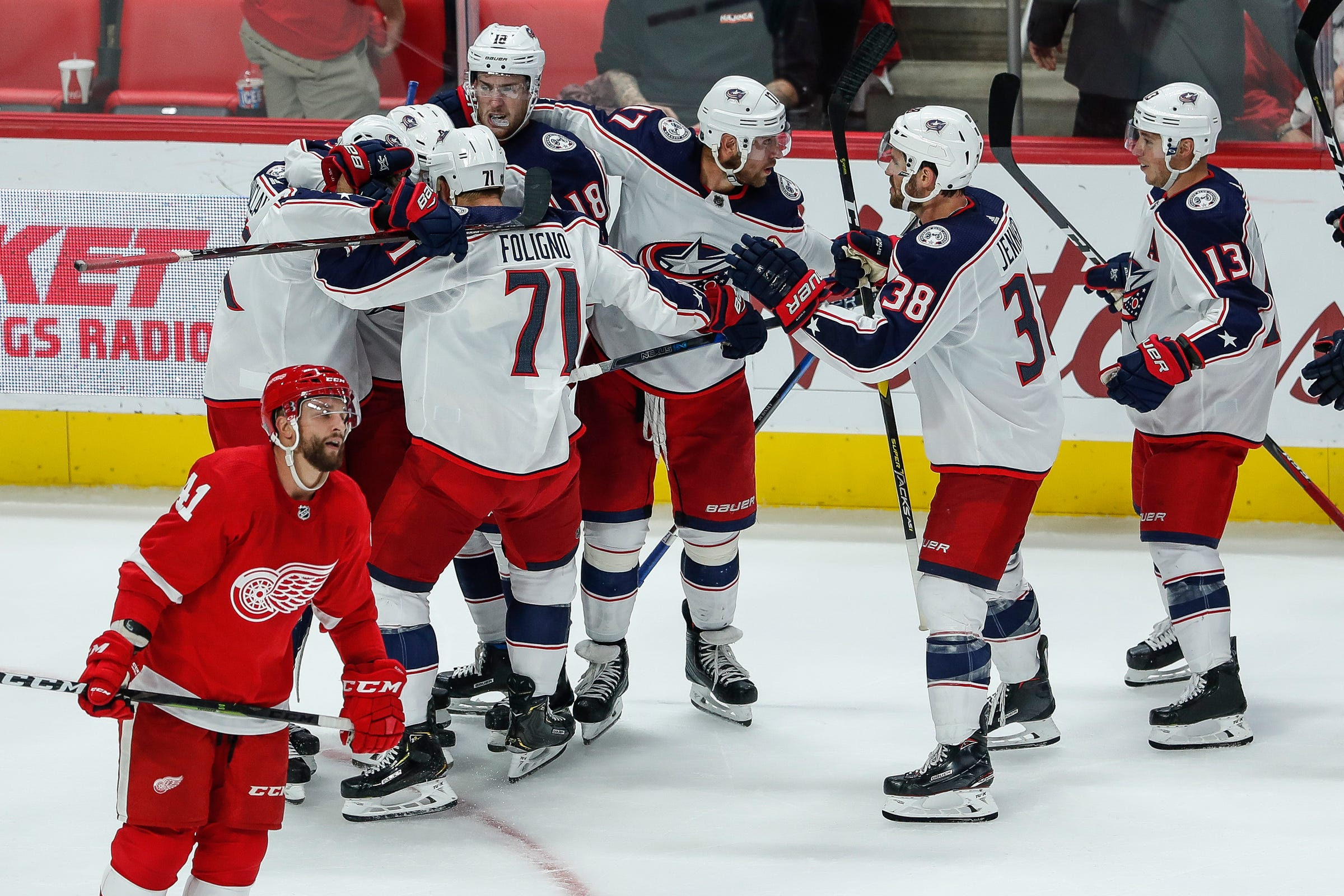 Red Wings forward Luke Glendening skates away as Blue Jackets players celebrate after the Wings' 3-2 overtime loss to the Blue Jackets on Thursday, Oct. 4, 2018, at Little Caesars Arena.