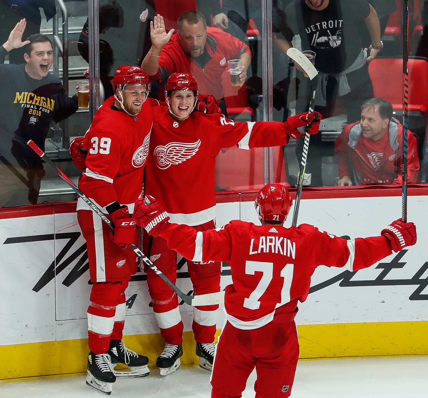 Red Wings forward Anthony Mantha (39), defenseman Dennis Cholowski (21) and forward Dylan Larkin (71) celebrate Cholowski's goal against the Blue Jackets during the second period at Little Caesars Arena on Thursday, October 4, 2018.