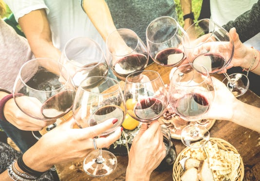 Friends Hands Toasting Red Wine Glass And Having Fun Outdoors Cheering With Winetasting Young People Enjoying Harvest Time Together At Farmhouse Vineyard Countryside Youth And Friendship Concept