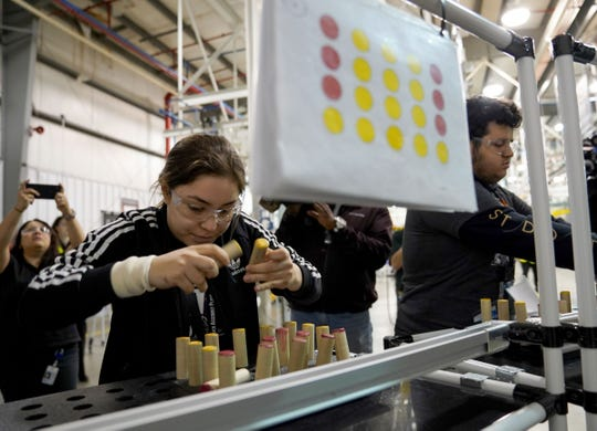 Emily Arellano from Sterling Heights High School flips pegs to match the displayed pattern teaching eye hand coordination during a challenge in the Work Hardening Center at FCA US Warren Truck Assembly Plant in Warren on Friday, October 5, 2018 as part of Manufacturing Day.