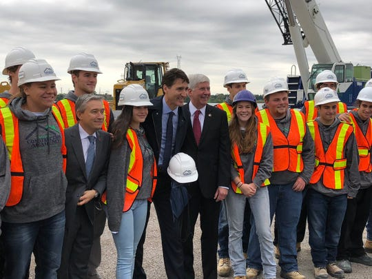 Canadian Prime Minister Justin Trudeau and Michigan Gov. Rick Snyder post for a photo with workers on the Windsor side of the Gordie Howe Bridge construction site.