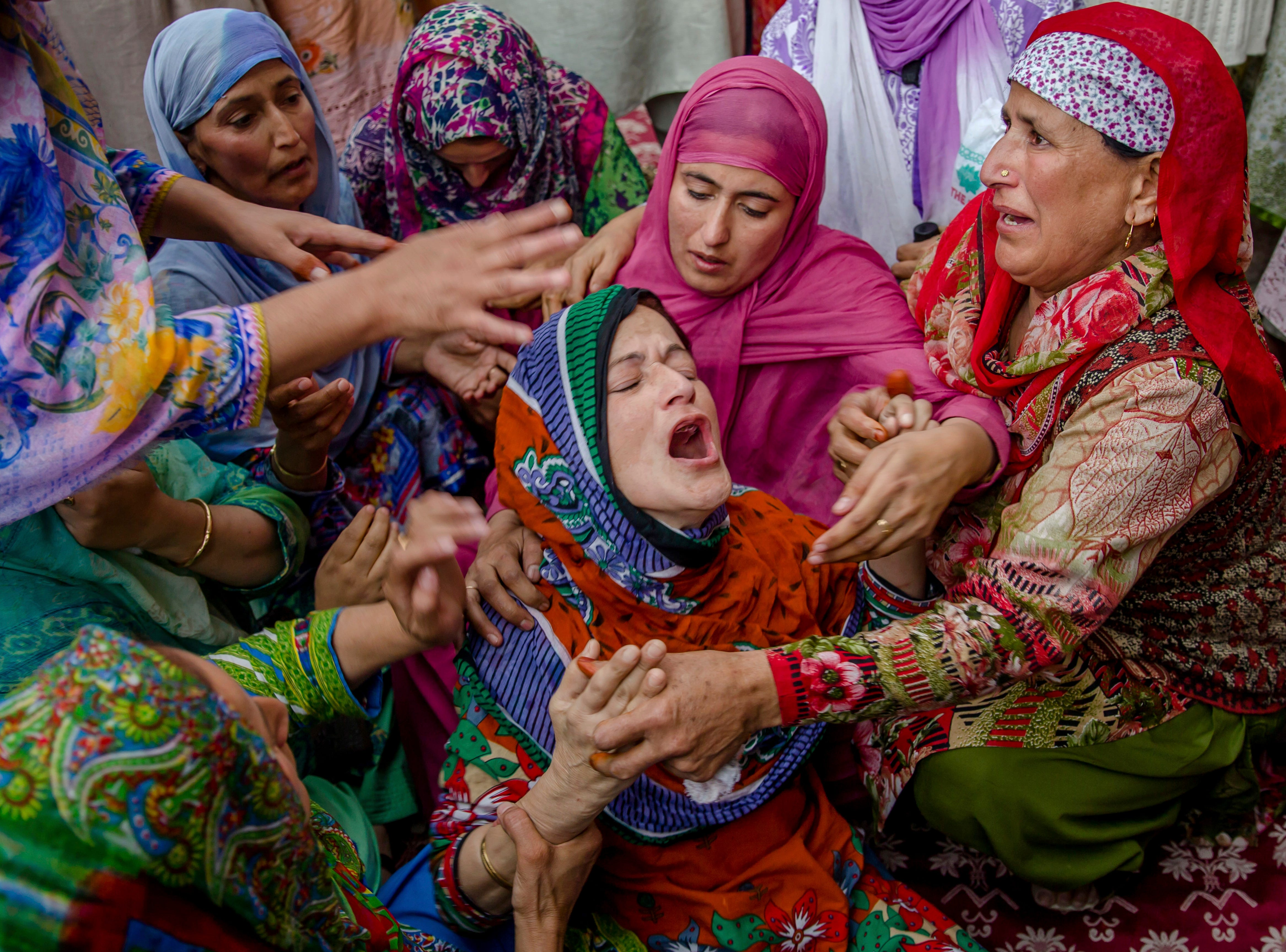Ruksana Nazir is comforted during the funeral of her husband, Nazir Ahmed Wani, in Srinagar, Indian-controlled Kashmir, Friday, Oct. 5, 2018. Suspected rebels on Friday shot and killed two activists, which included Wani, affiliated with a pro-India Kashmiri political group in the disputed region's main city, officials said.