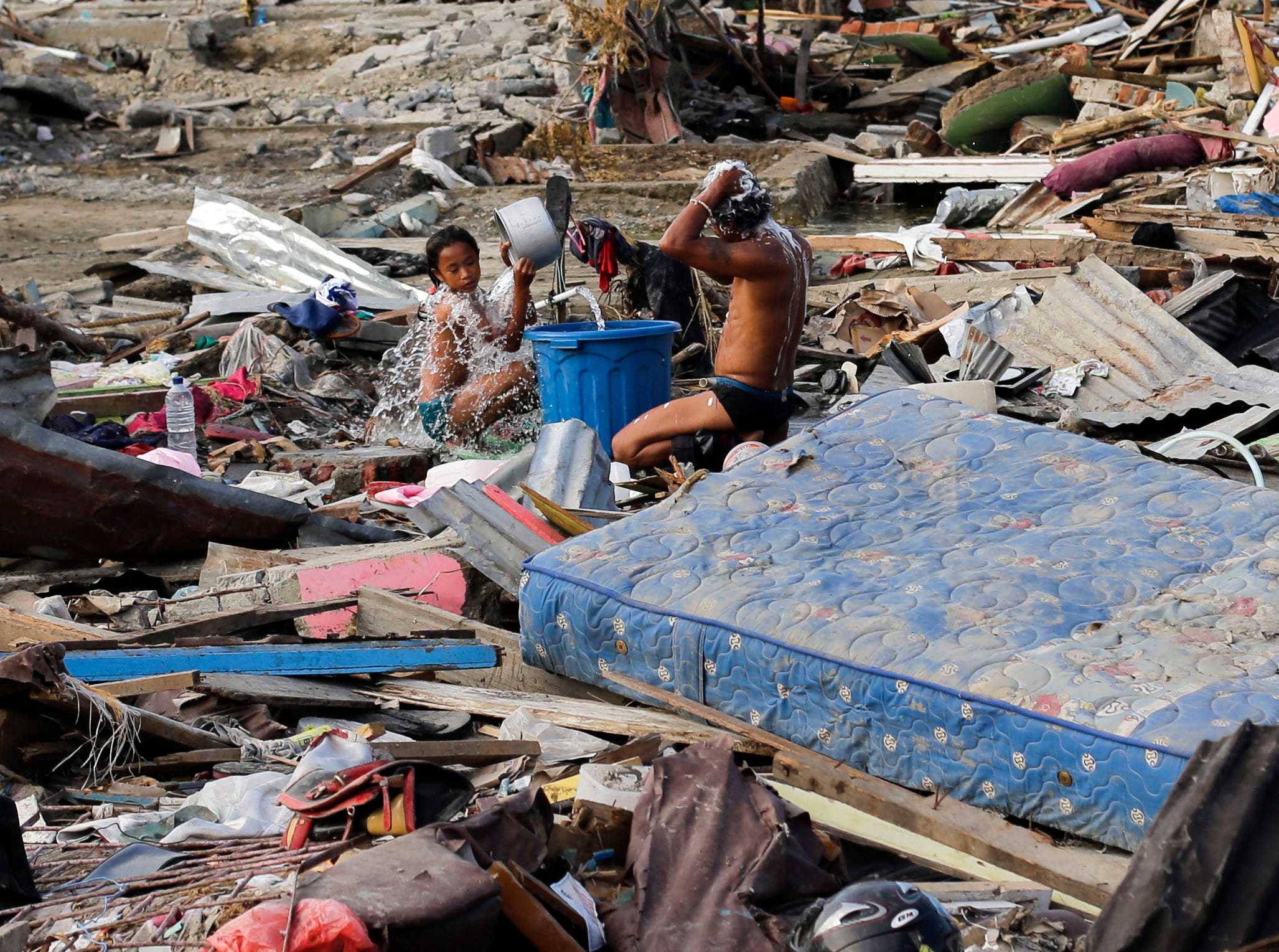 Residents take a bath amidst remains of toppled homes and structures in Palu, Central Sulawesi, Indonesia on Friday, Oct. 5, 2018. As the sun slipped behind the mountains and a gentle breeze blew onshore, hundreds of people gathered on an Indonesian beach Friday to chant a Muslim prayer and remember those they lost one week after a massive earthquake and tsunami ravaged the area, killing more than 1,500 people.