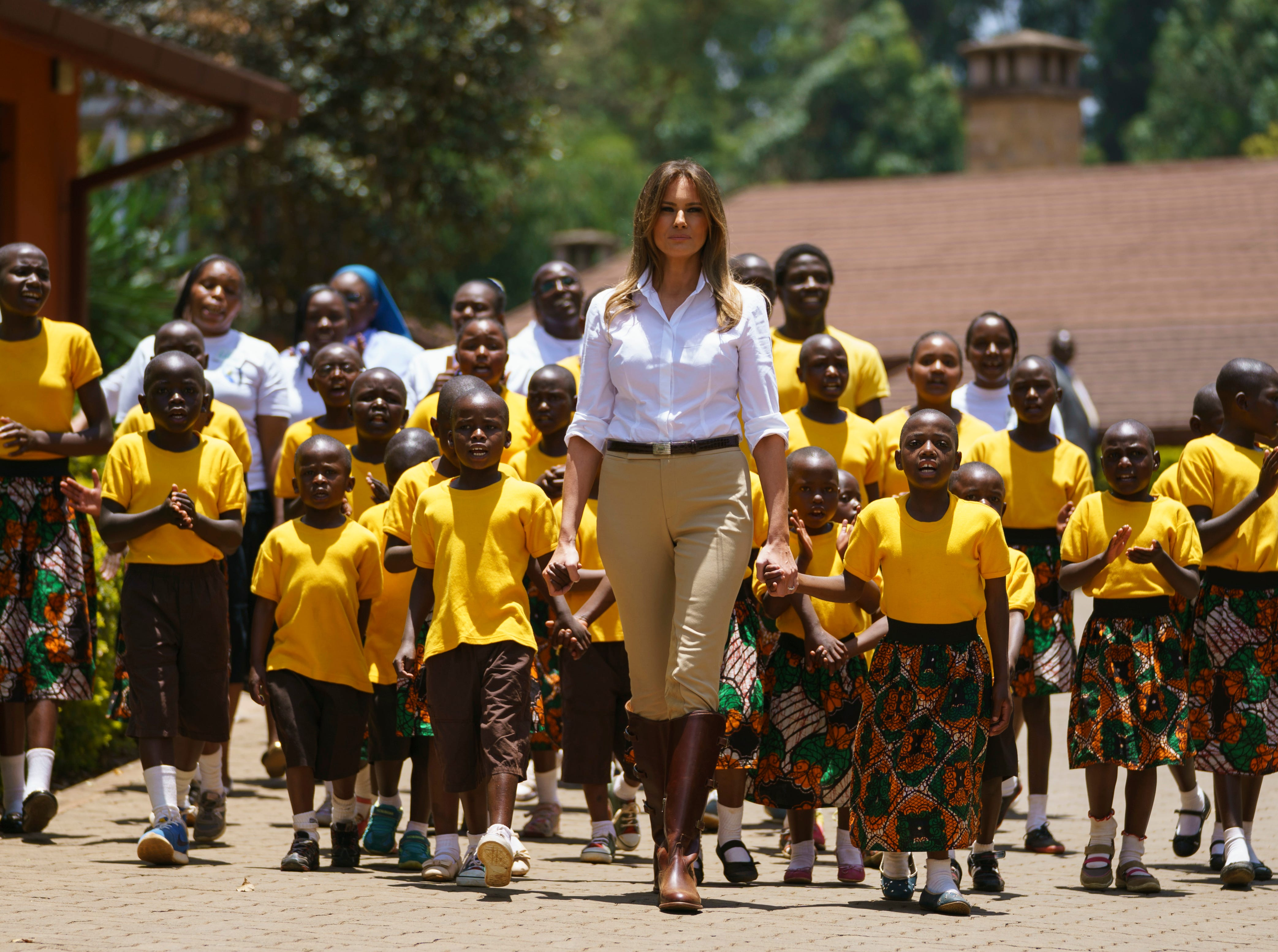 Melania Trump walks with singing children while visiting the Nest Orphanage in Limuru, Kenya, Friday, Oct. 5, 2018. She also has fed baby elephants as she visits a national park in Kenya to highlight conservation efforts, and  went on a quick safari. Mrs. Trump is on her first-ever visit to Africa, and her first extended solo international trip as first lady.