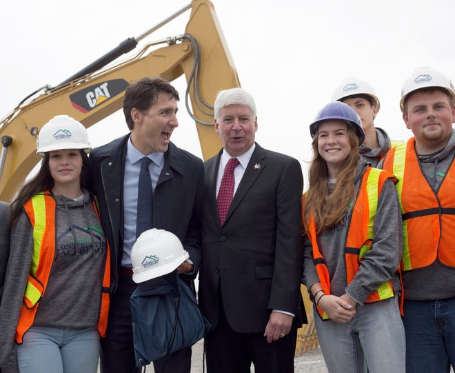 Canadian Prime Minister Justin Trudeau, second from left, and  Gov. Rick Snyder, center,  pose with construction apprenticeship students  Frida, in Windsor, Ontario, where they announced that the Gordie Howe Bridge, a multibillion-dollar construction project to build a link between Detroit and Windsor, is officially underway.
