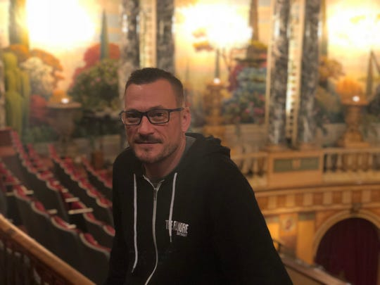 Fillmore Detroit general manager Ben Doughty sits near the restored murals inside the 93-year-old theater.
