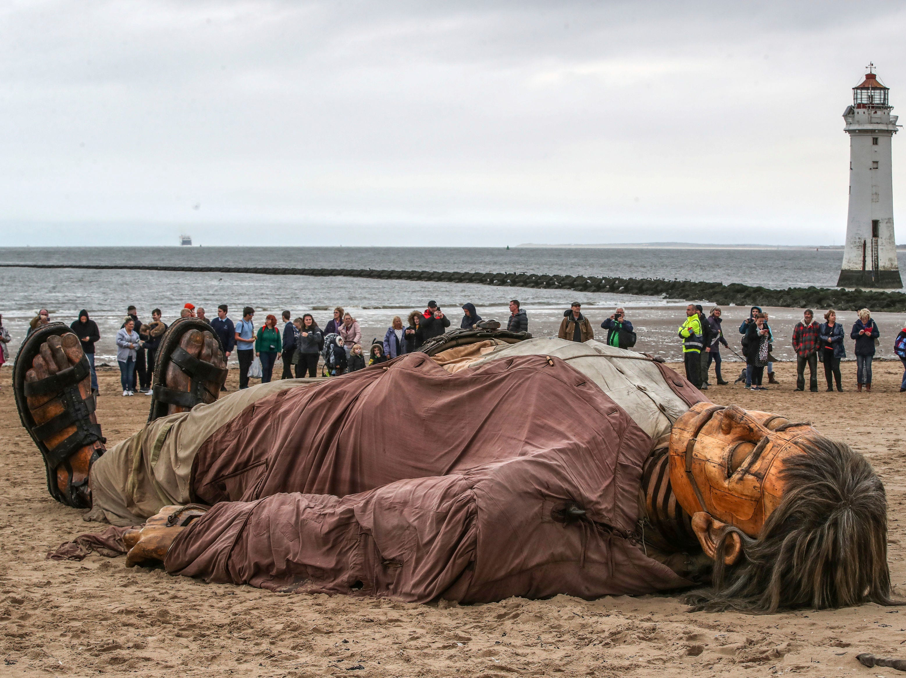 """Puppet """"Giant Man"""" lays on the beach in New Brighton, part of the Royal De Luxe Giant Spectacular over the weekend, in Wirral, England, Friday, Oct. 5, 2018."""