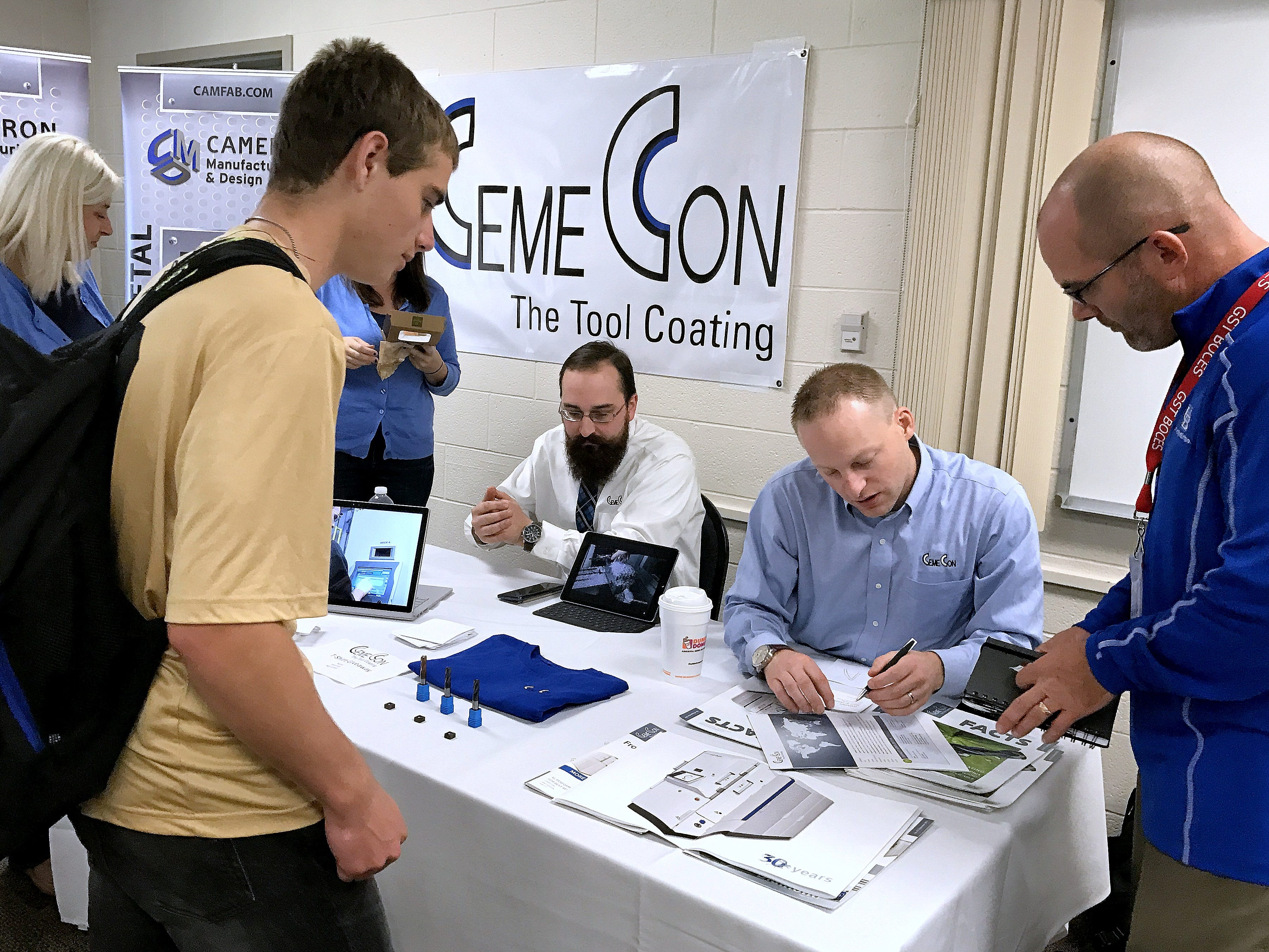Representatives from CemeCon in Big Flats talk about the process they use to coat cutting tools to make them more durable during Manufacturing Day on Friday.