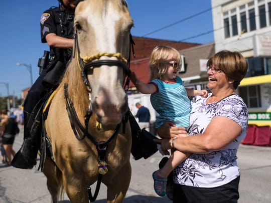 "Sgt. Tyrone Wood, top left to right, allows Bethany Slade, 2, and her grandmother Denise Farmer to pet Blondie, an Evansville Police Department horse, during the 97th annual West Side Nut Club Fall Festival on West Franklin Street in Evansville, Ind., Wednesday, Oct. 3, 2018. ""She's a fourth generation fall festival goer,"" Farmer said about her granddaughter Slade, while smiling from ear to ear."