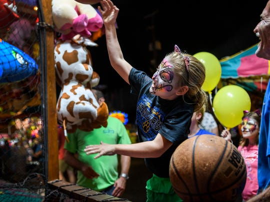 Karaline Hoehn, 8, plays Hotshots Streetball as her family intently watches during the 97th annual West Side Nut Club Fall Festival on West Franklin Street in Evansville, Ind., Wednesday, Oct. 3, 2018.