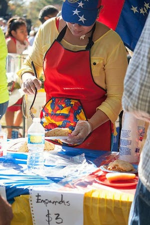 Cooks at a Colombian booth at Fiesta Evansville serve empanadas, fried dough pies with a variety of fillings.
