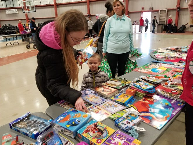 Shawnelle Miller and her son Anthony Cantu search for a present during the Community Christmas program last year at Terra State Community College.