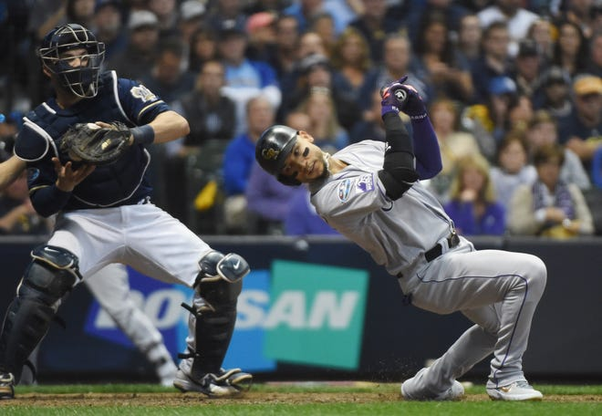 Oct 4, 2018; Milwaukee, WI, USA;  Colorado Rockies outfielder Carlos Gonzalez (5) ducks away from an inside pitch in the 10th inning against the Milwaukee Brewers in game one of the 2018 NLDS playoff baseball series at Miller Park. Mandatory Credit: Benny Sieu-USA TODAY Sports