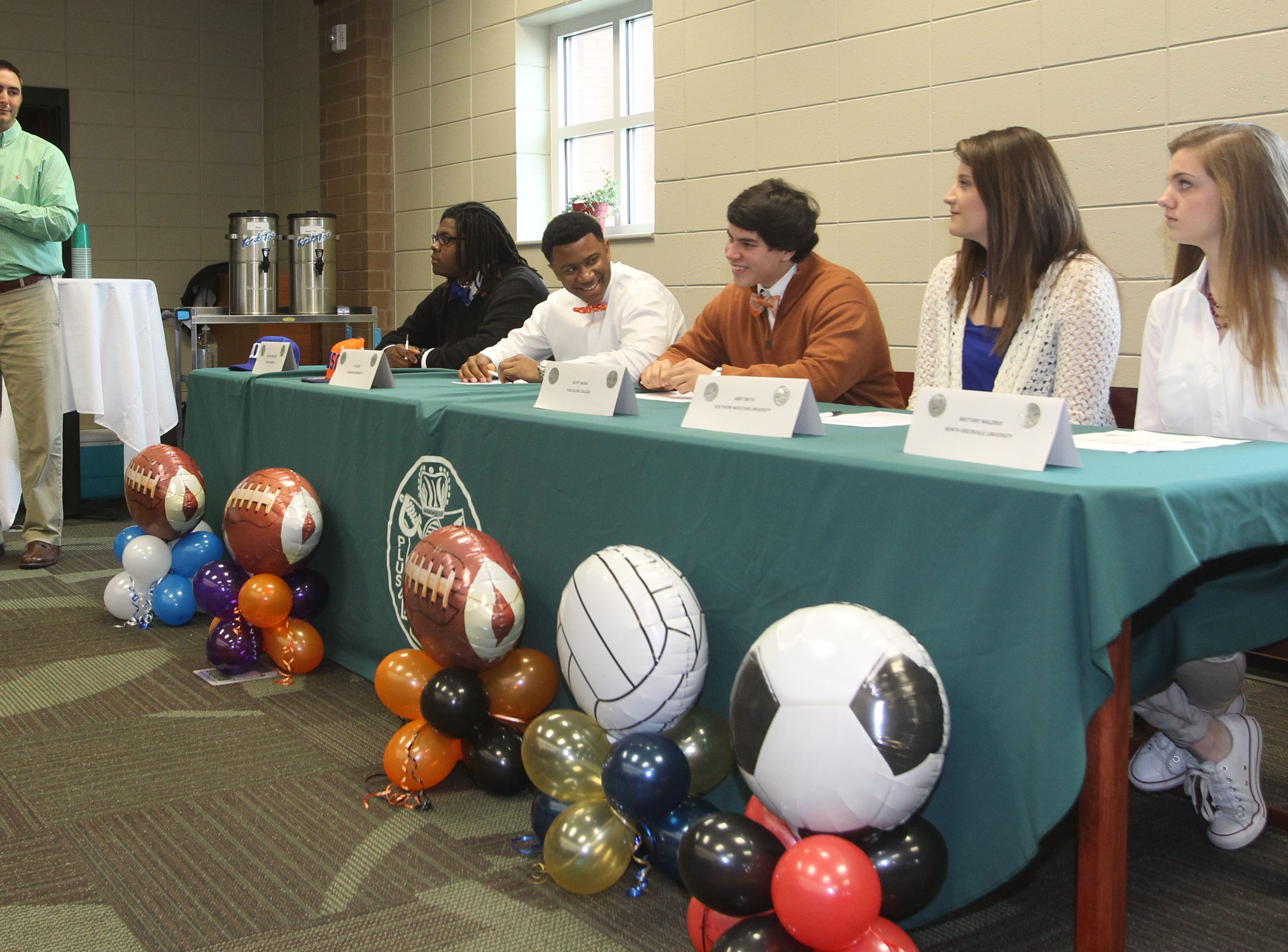 C.J. Fuller, second from left at the table, participates in National Signing Day at Easley High School during his senior year.
