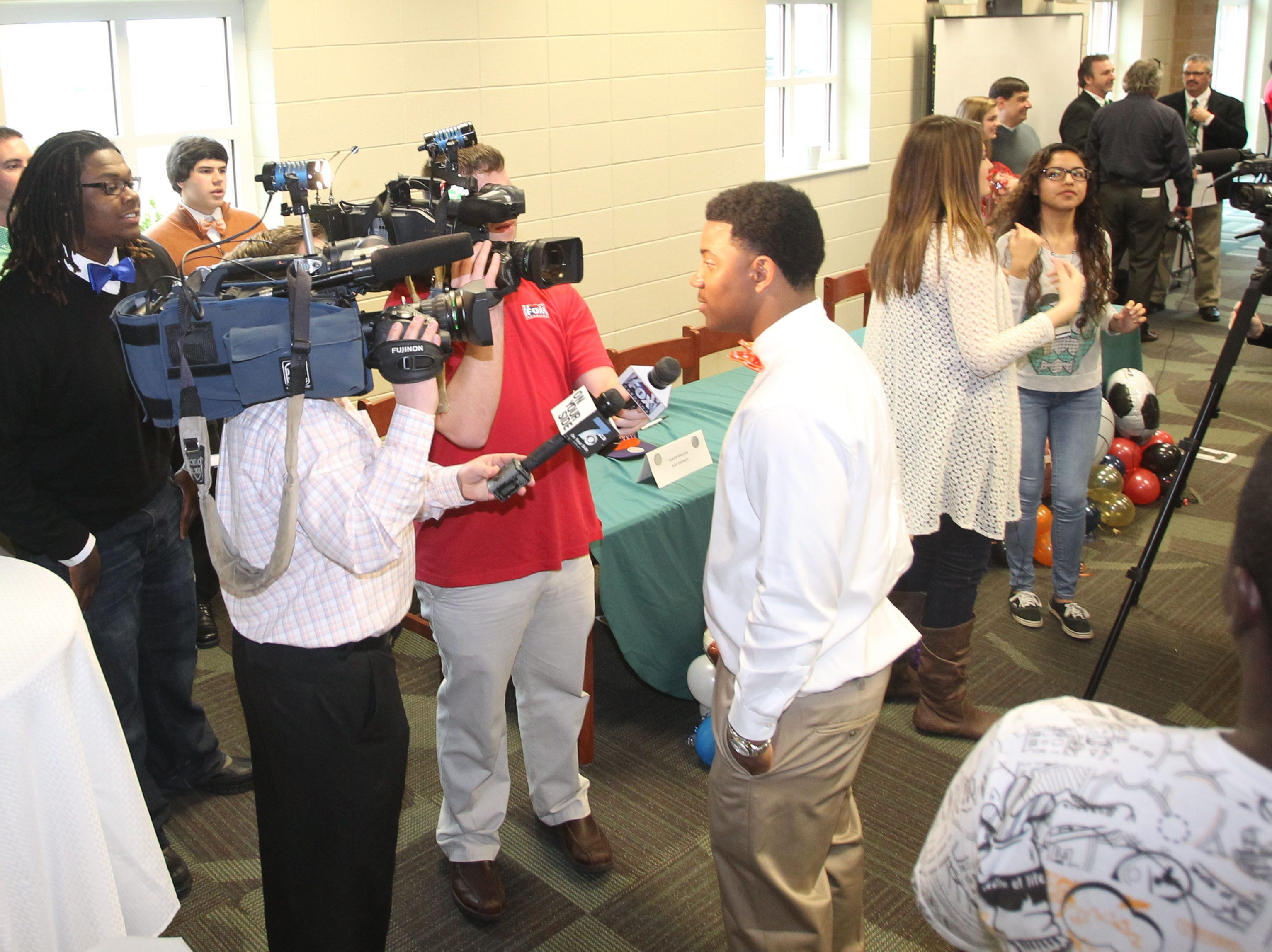 C.J. Fuller, center, participates in National Signing Day at Easley High School during his senior year.
