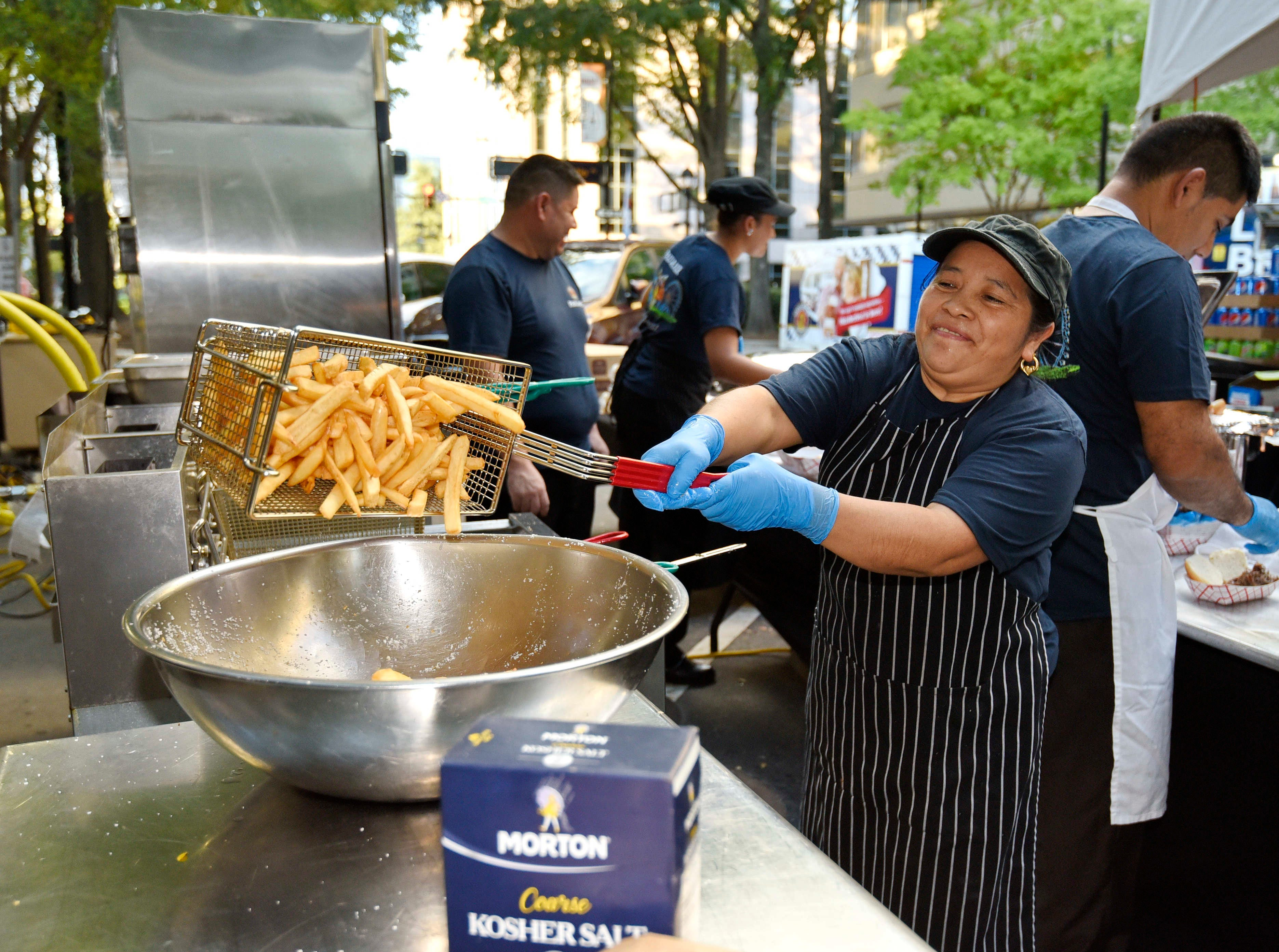 Workers make the fries during Oktoberfest which kicked off at NOMA Square in downtown Greenville Thursday, Oct. 4,  2018.