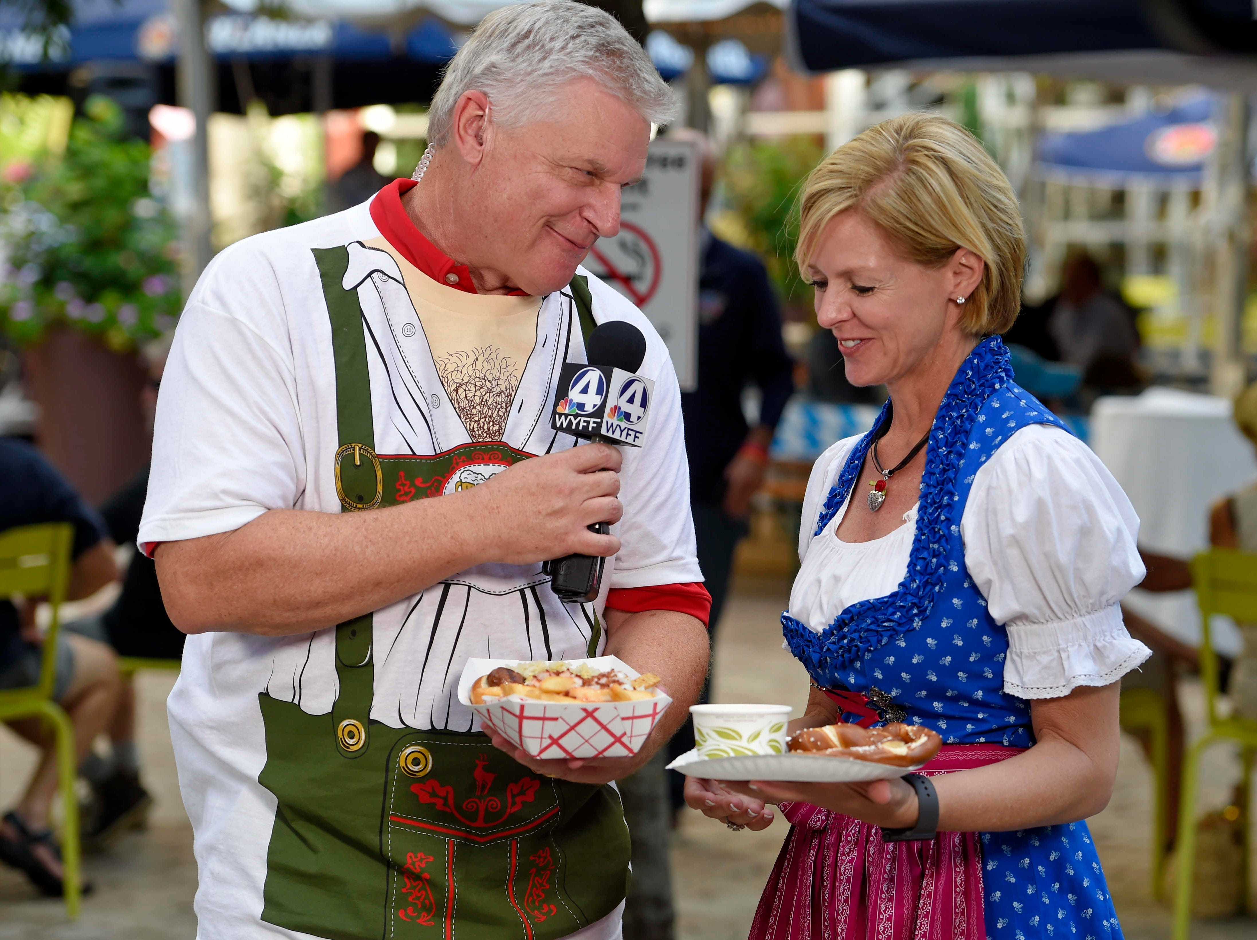Heather Meadors of Auro Hotels, presents WYFF's John Cessarich some German food during which kicked off at NOMA Square in downtown Greenville Thursday, Oct. 4,  2018.