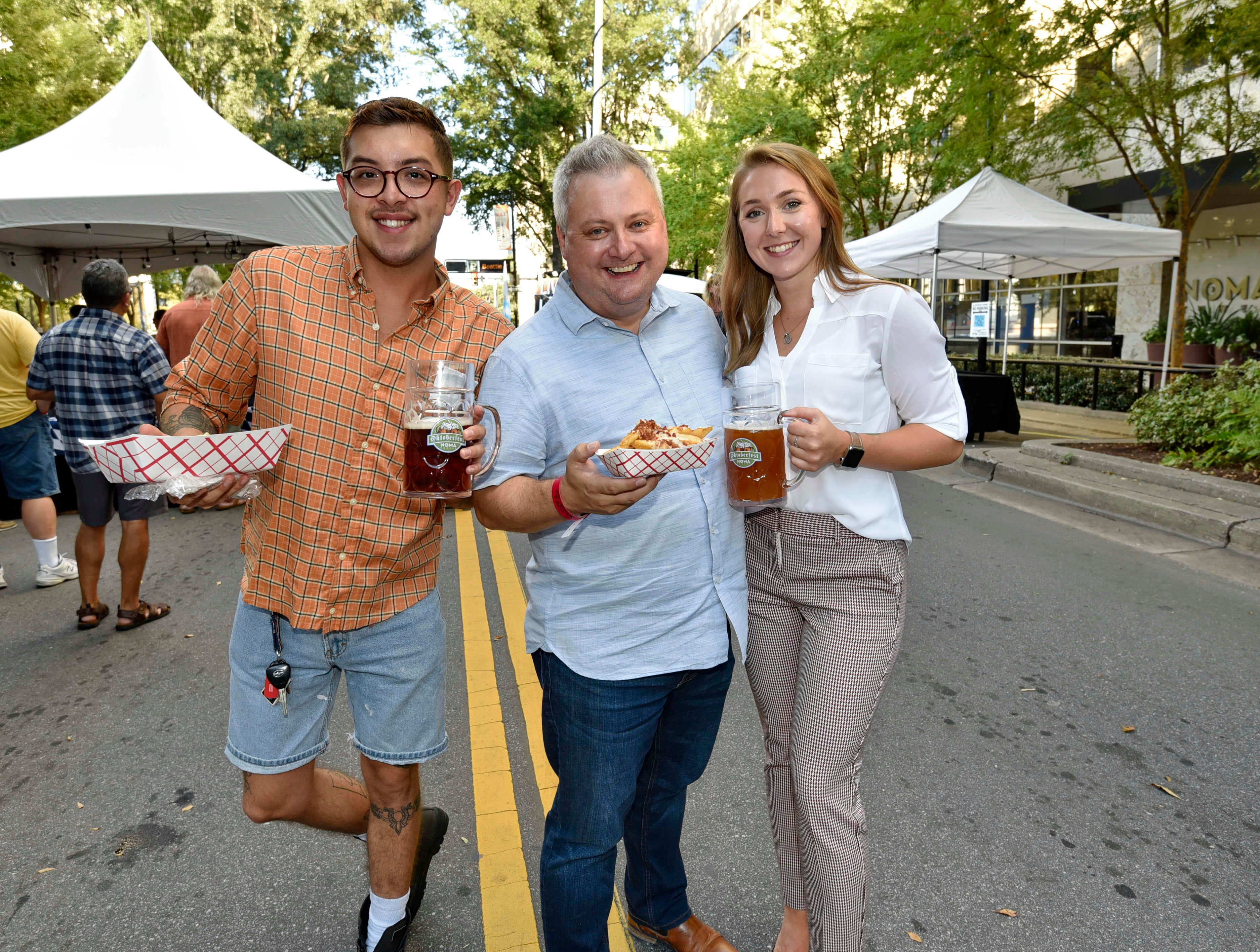 Matthew Gutierrez, Jonathan Brashier, and Erin Ogletree attend Oktoberfest which kicked off at NOMA Square in downtown Greenville Thursday, Oct. 4,  2018.