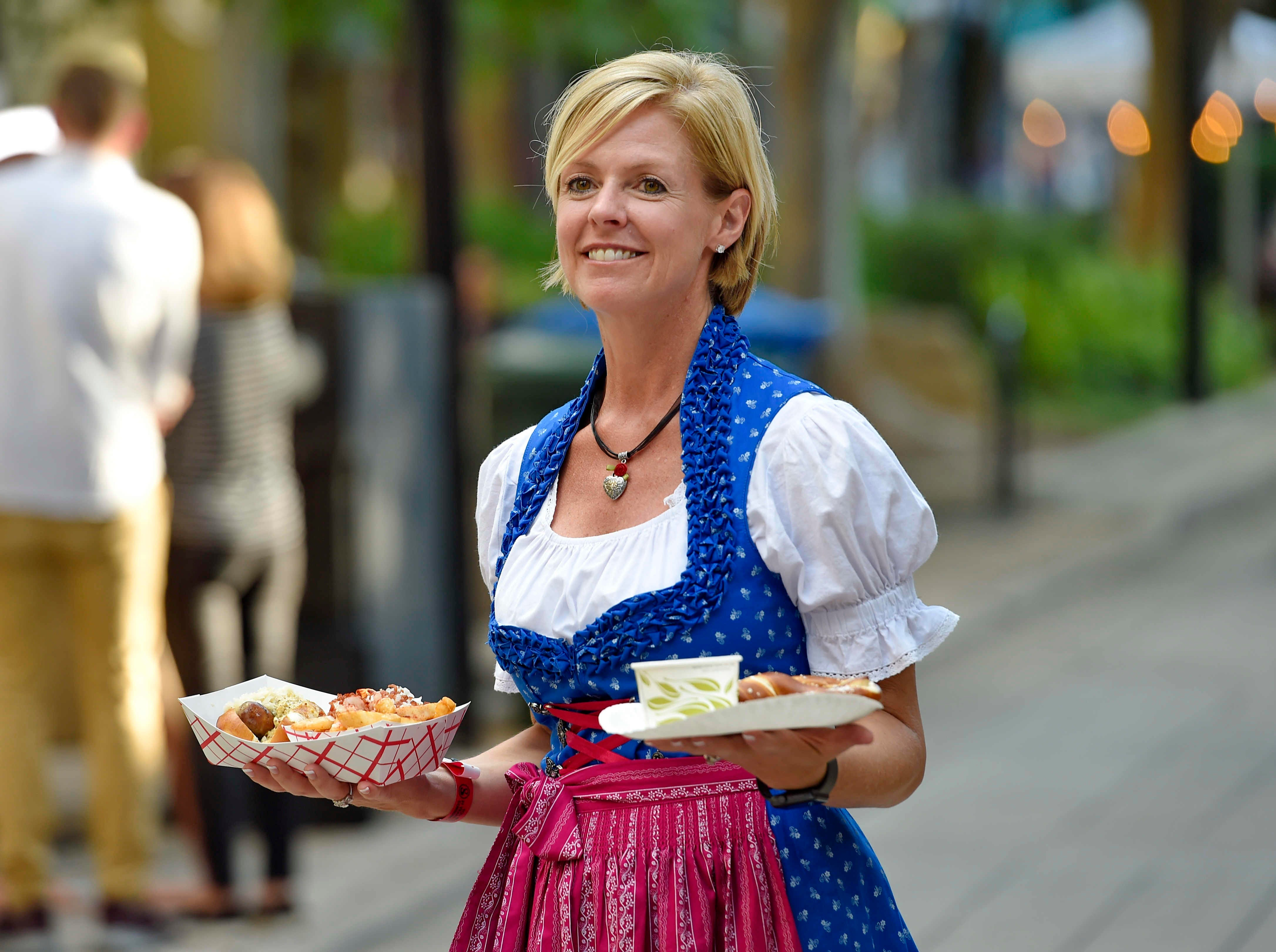 Heather Meadors of Auro Hotels, carries plates of German food during Oktoberfest,  which kicked off at NOMA Square in downtown Greenville Thursday, Oct. 4,  2018.