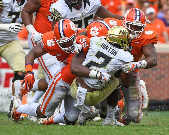 In this 2017 file photo, from left, Clemson defensive lineman Christian Wilkins (42), defensive lineman Clelin Ferrell (99), and defensive lineman Austin Bryant (7) bring down Wake Forest quarterback Kendall Hinton (2).