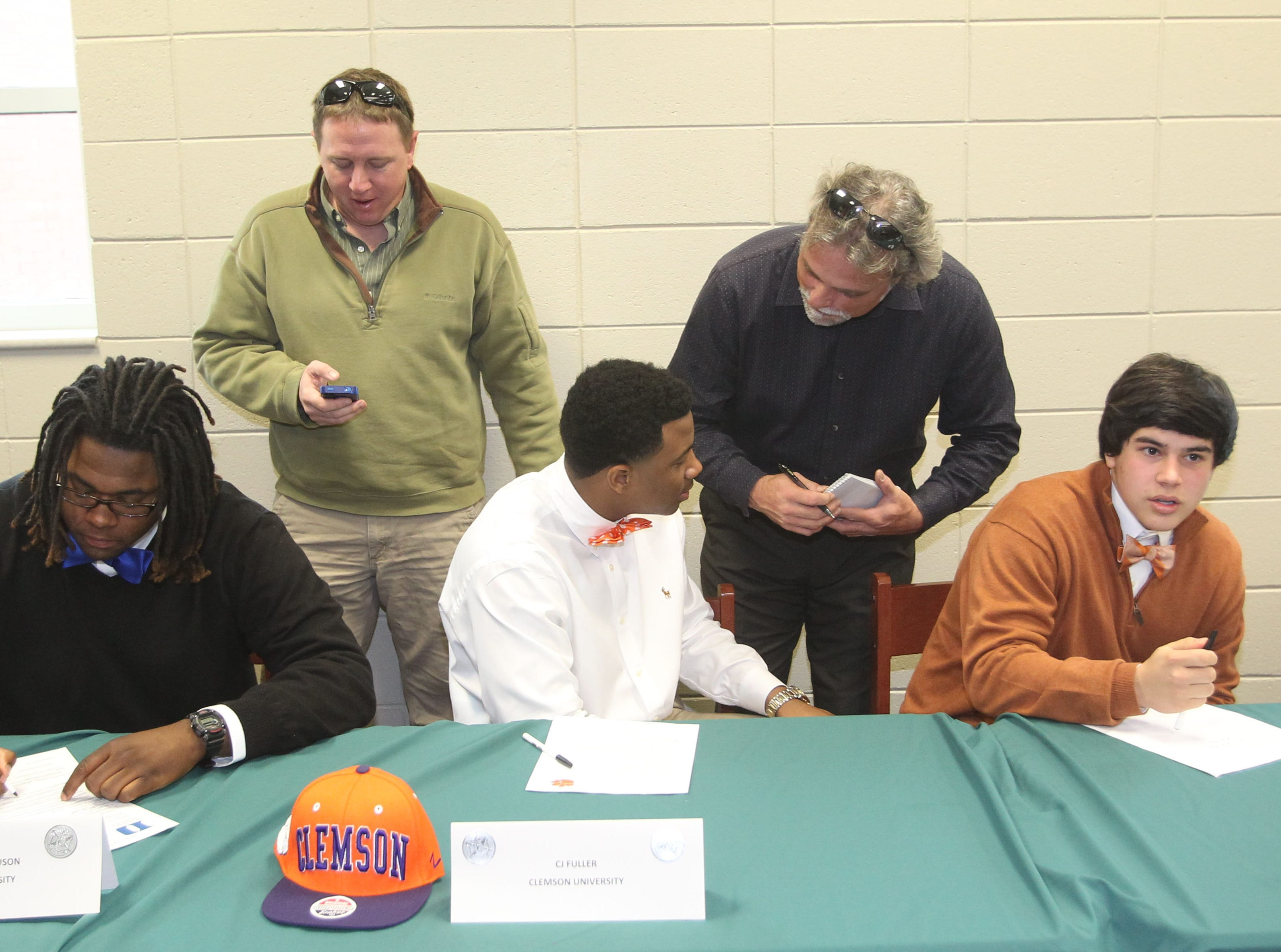 C.J. Fuller, middle, participates in National Signing Day at Easley High School during his senior year.