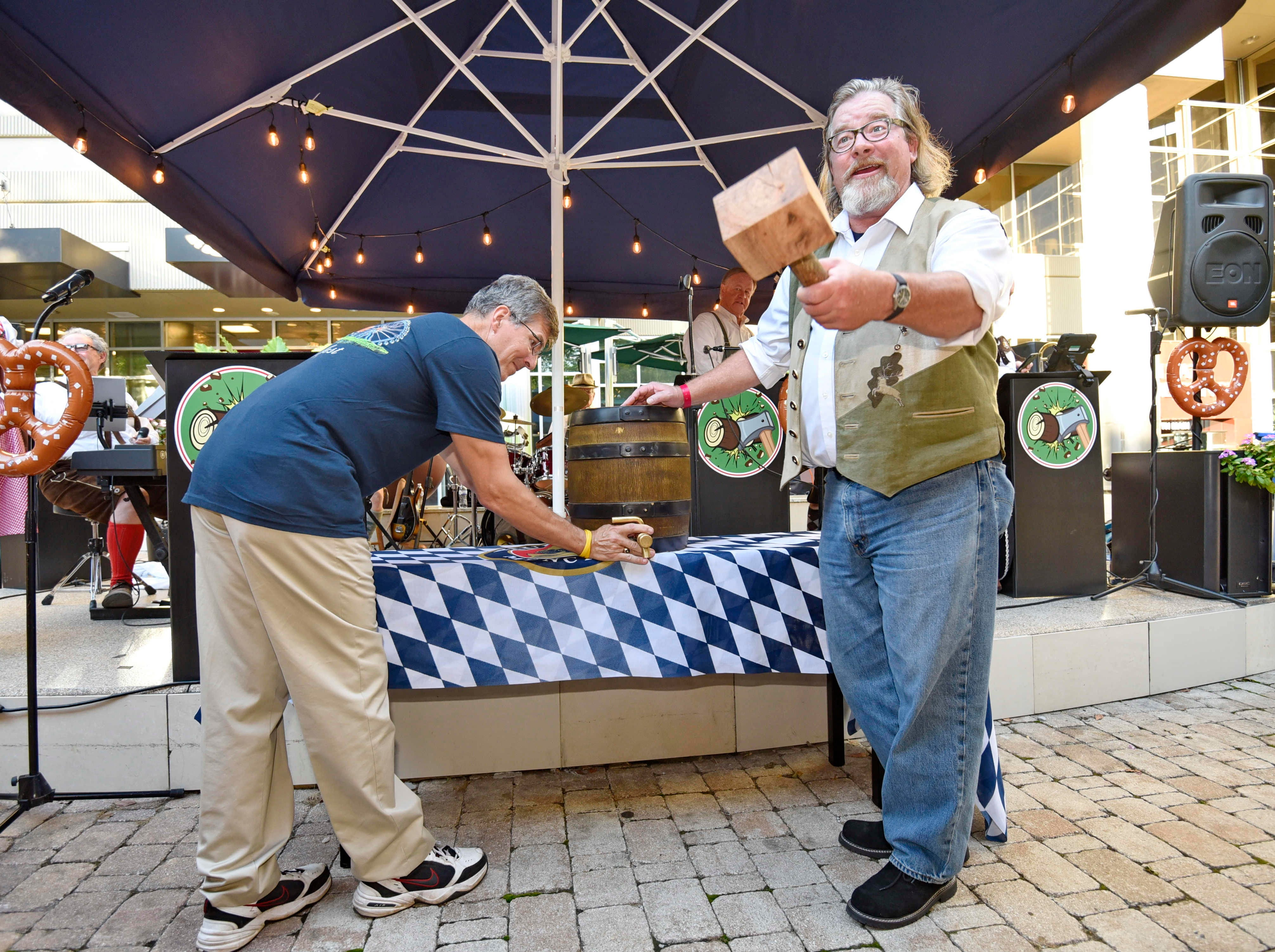 Jay Spivey of FETE Greenville, right, and Mel Arce tap the official keg to kick off Oktoberfest at NOMA Square in downtown Greenville Thursday, Oct. 4,  2018.