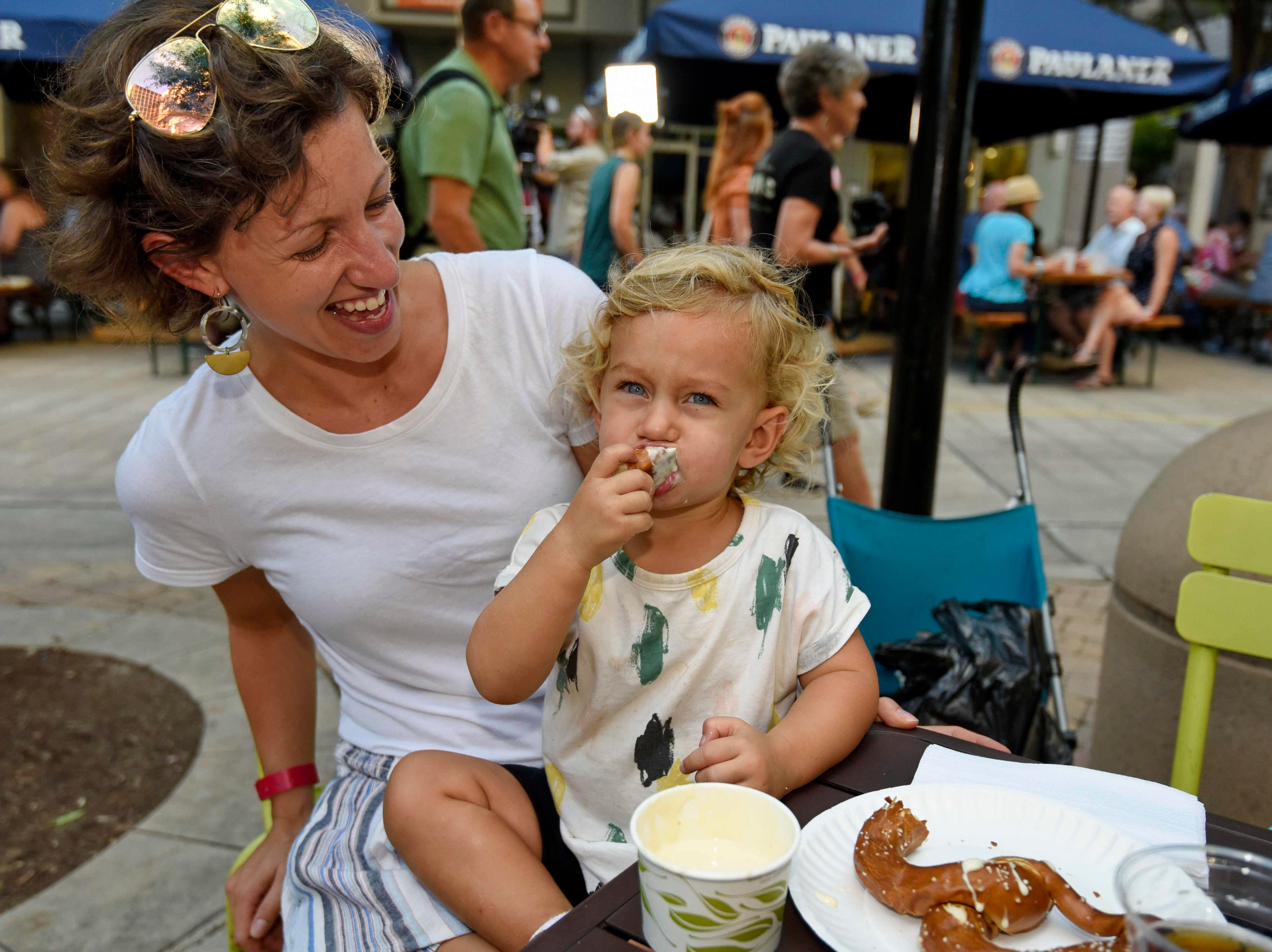 Cora Thomas, age 2, enjoys her pretzel and cheese with her mother Amamnda during Oktoberfest which kicked off at NOMA Square in downtown Greenville Thursday, Oct. 4,  2018.