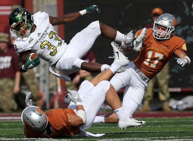Sacramento State's Elijah Dotson flies over Montana safety Reid Miller, left, and Montana safety Robby Hauck (17) earlier this fall at Washington-Grizzly Stadium in Missoula.
