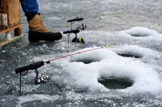 An angler patiently waits for a bite on one of his ice fishing poles in 2018 at Holter Lake.