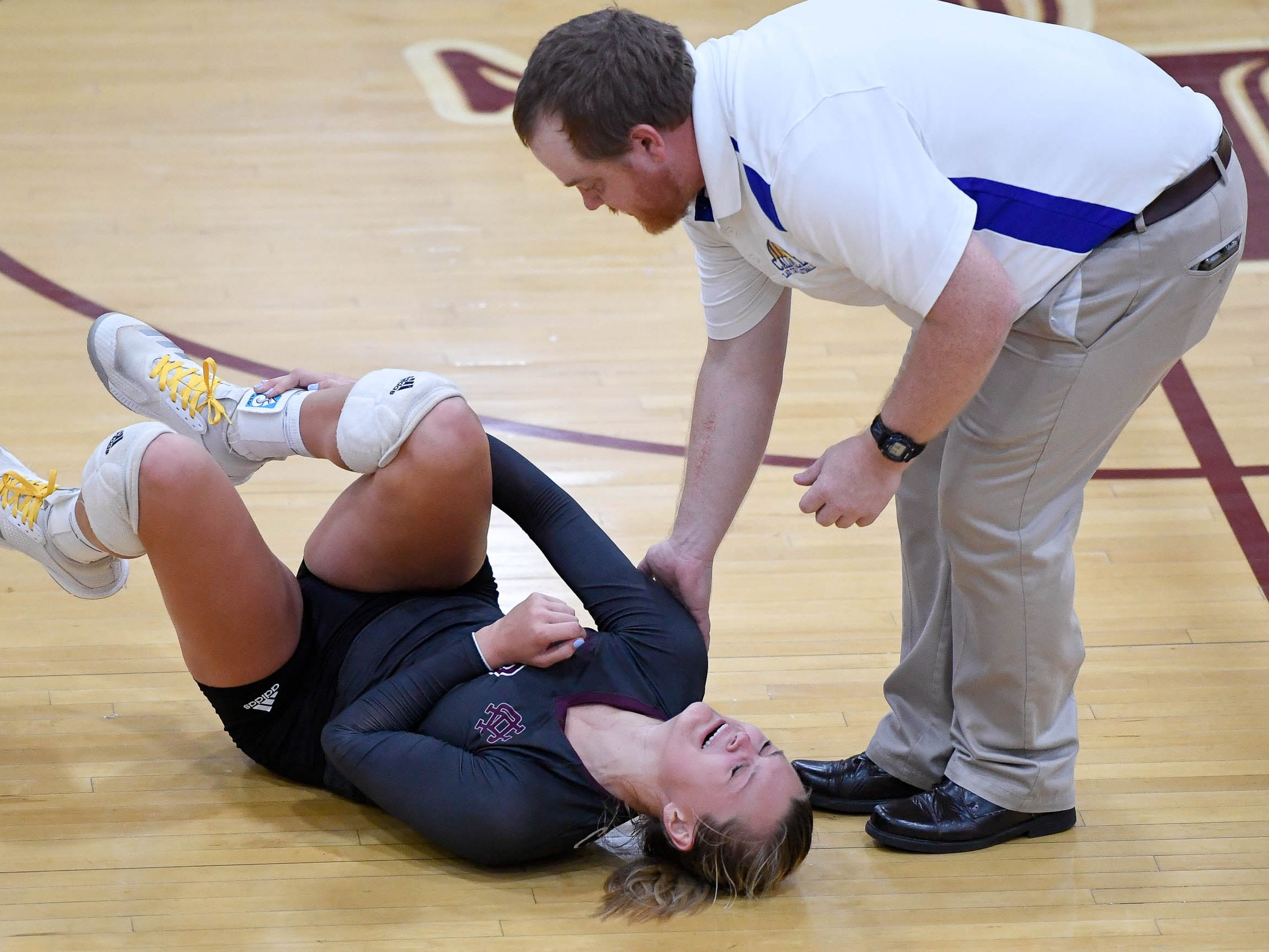 Lady Tiger head coach Daniel Cortner assists Henderson's Hannah Watkins (3) who was injured in the third game as the Henderson County Lady Colonels play the Caldwell County Lady Tigers at Colonel Gym Thursday, October  4, 2018.