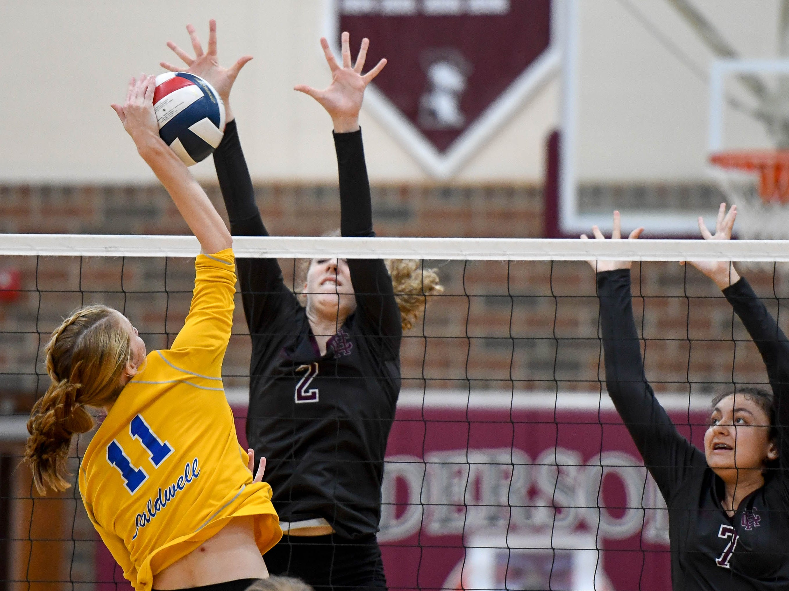 Henderson's Brooke Springer (2) and Henderson's Kaylee Stott (7) jump to block a shot from Caldwell's Abby Griggs (11) as the Henderson County Lady Colonels play the Caldwell County Lady Tigers at Colonel Gym Thursday, October  4, 2018.