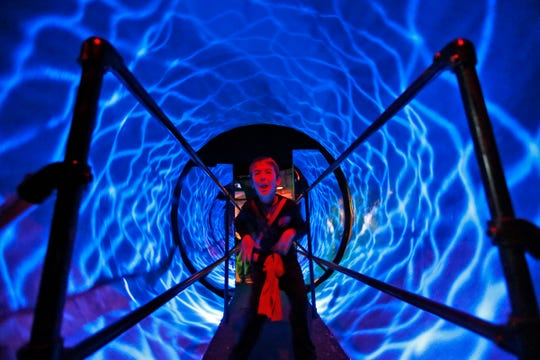 """Luke Amos makes a face while walking through the spinning tunnel in the """"Grim-nasium!"""" haunted house at the Children's Museum of Indianapolis, Friday, Oct. 5, 2018.  The sports-themed and creepy but popular haunted house runs Oct. 11-31, 2018, except for Mondays."""