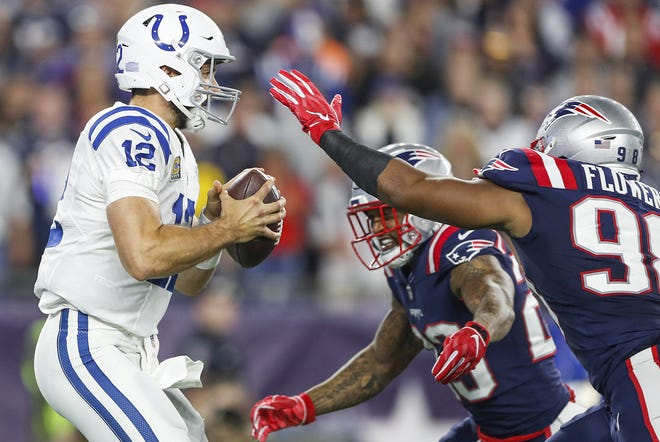 Indianapolis Colts quarterback Andrew Luck (12) is sacked by New England Patriots defensive back Patrick Chung (23) and defensive end Trey Flowers (98) in the first quarter at Gillette Stadium in Foxborough, Mass., Thursday, Oct. 4, 2018.