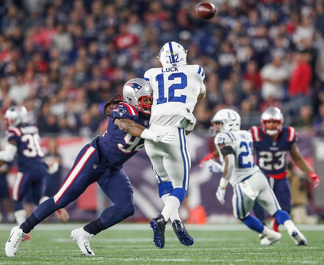 New England Patriots defensive end Adrian Clayborn (94) pressures Indianapolis Colts quarterback Andrew Luck (12) who throws an interception to New England Patriots defensive back Patrick Chung (23) in the second quarter at Gillette Stadium in Foxborough, Mass., Thursday, Oct. 4, 2018.