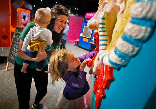 """Megan Hinders, holding her son Pierson, laughs as her daughter Evelynn tries to grab a jewel in this perception and illusion interactive, in the """"Science of Ripley's Believe It or Not!"""" exhibit at the Children's Museum of Indianapolis, Friday, Oct. 5, 2018.  The optical illusion makes it a hard task to grab the jewel."""