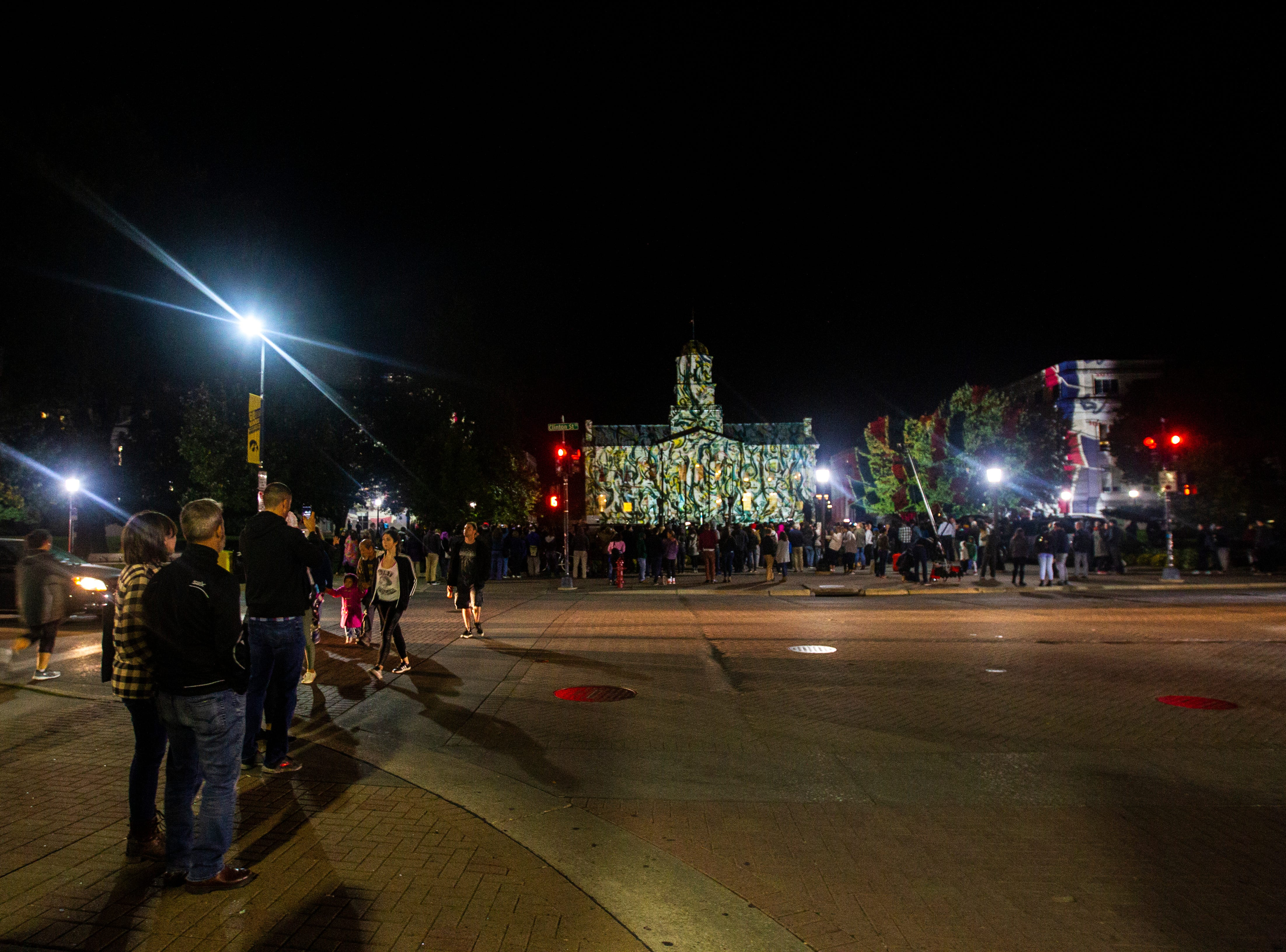 Gerry Hofstetter, a light artist, projects images onto the Old Capitol on Thursday, Oct. 4, 2018, on the Pentacrest in Iowa City.