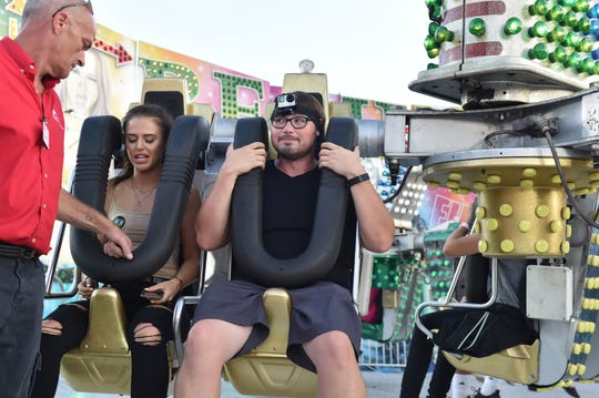 Searching for reassurance, Clarion Ledger reporter Tyler Cleveland (right) looks to the operator of the 'Remix' ride at the159th Mississippi State Fair. Wednesday, Oct. 3, 2018.