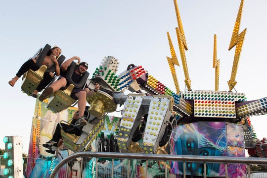 Clarion Ledger reporters Mackenzie Salmon and Tyler Cleveland are slung around on the 'Remix', another scary staple of the midway at the annual Mississippi State Fair in Jackson. Wednesday, Oct. 3, 2018.