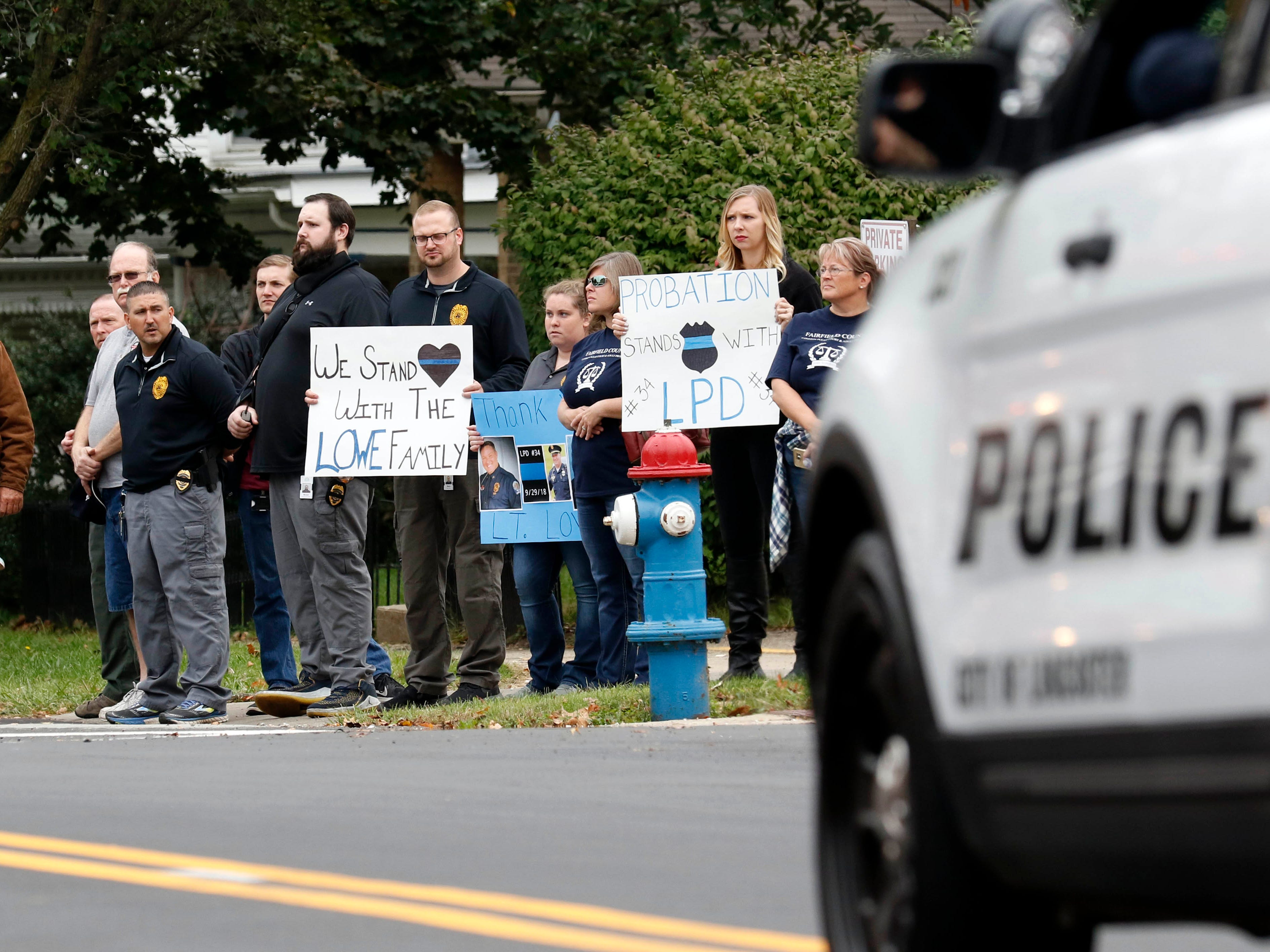 Members of the Fairfield County Common Please Court Adult Community Control Department stand along Chestnut Street as a funeral procession of more than 100 vehicles drive through the streets of Lancaster Friday, Oct. 5, 2018. The procession was for Lancaster Police Lt. Brian Lowe, who died unexpectedly September 29 while off duty.