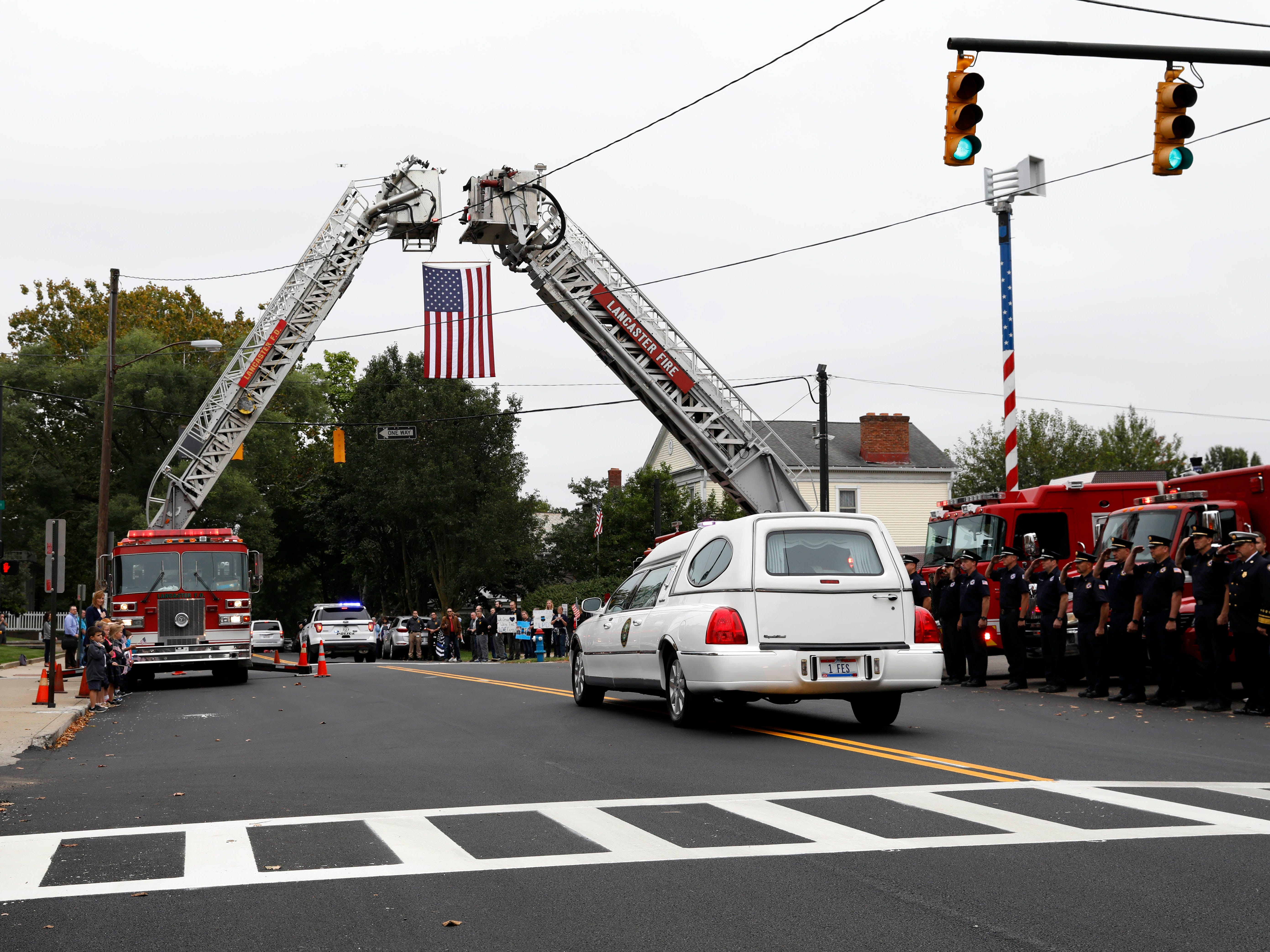 A hearse carrying the casket of Lancaster Police Lt. Brian Lowe passes under an American flag hanging between two Lancaster Fire Department trucks Friday, Oct. 5, 2018, on Chestnut Street in Lancaster. More than 100 cars about half of them police and emergency services vehicles from throughout Ohio took part in the procession from Fairfield Christian Church on North Columbus Street to Maple Grove Cemetery on U.S. 22 just east of the city. Lowe died unexpectedly September 29 while off duty, he was 46. He leaves behind a wife and two children.