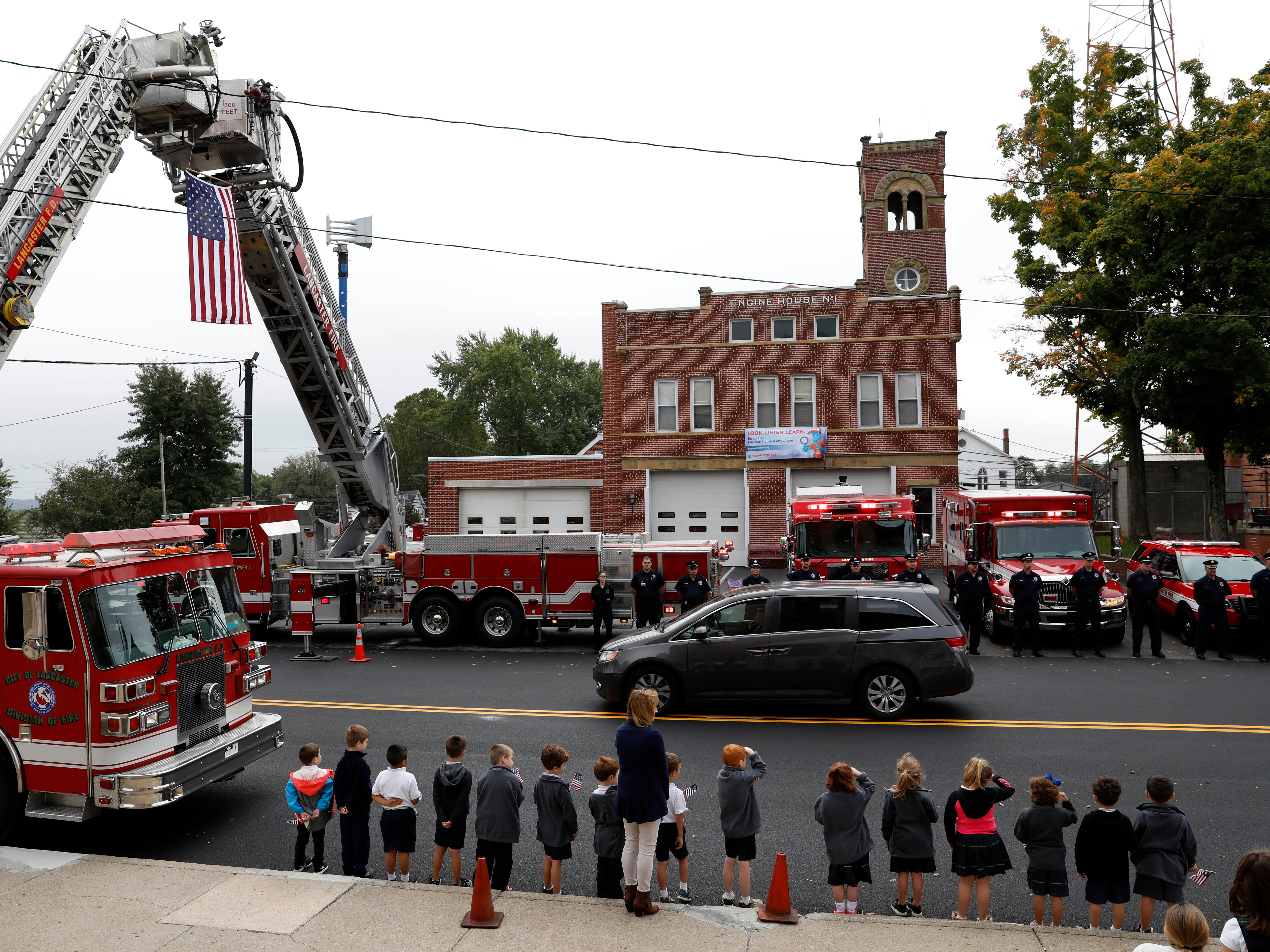 Students from St. Mary School stand on one side of Chestnut Street while Lancaster firefighters stand across from them as the funeral procession for Lancaster Police Lt. Brian Lowe drives down the street Friday, Oct. 5, 2018, in Lancaster. All of the schools students in pre-kindergarten through eighth grade stood outside to honor Lowe who died unexpectedly September 29 while off duty.