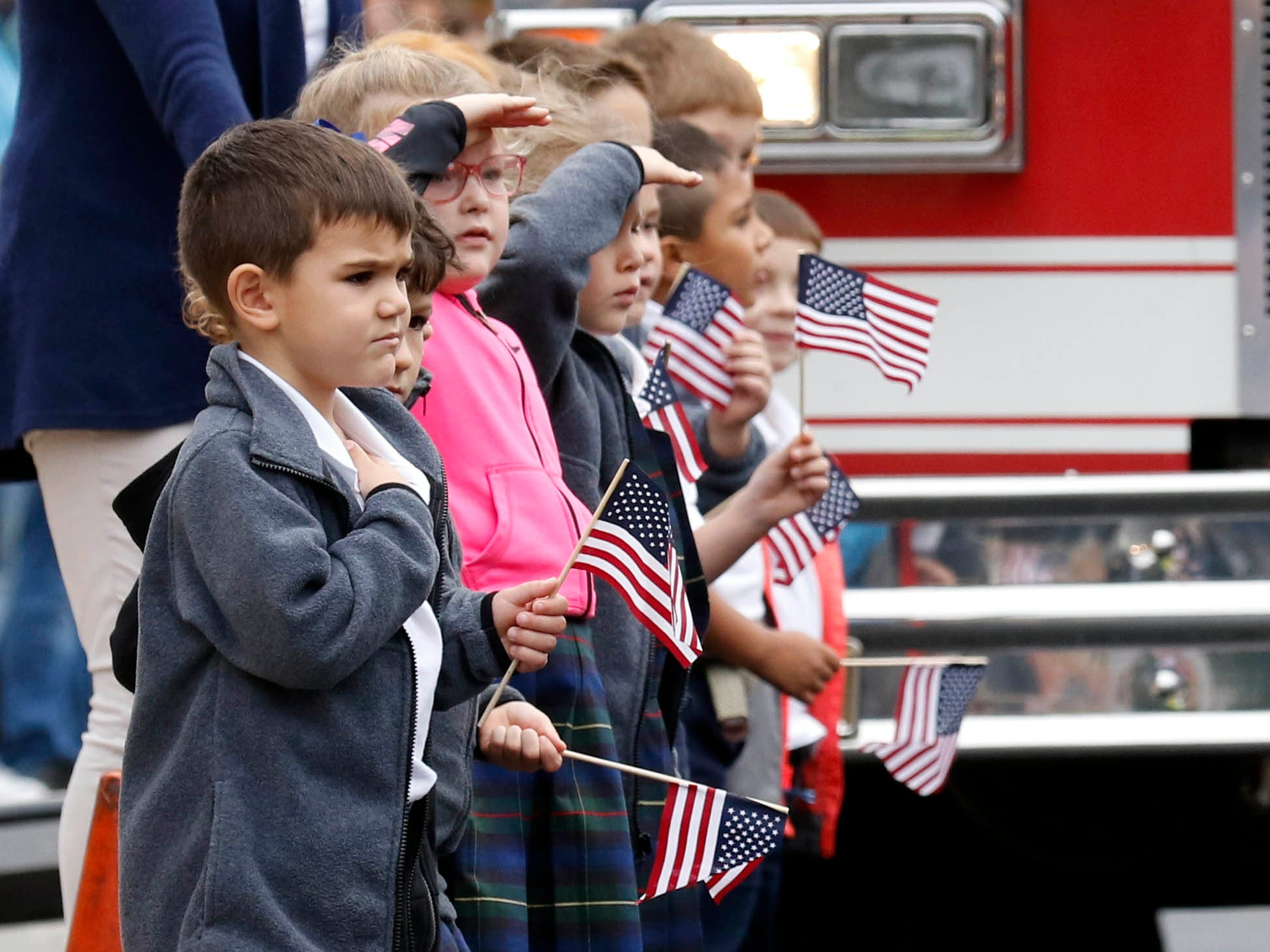 Camden O'Rielley, Evie Gabbard and the rest of their kindergarten class stand outside St. Mary School Friday, Oct. 5, 2018, as they watch the funeral procession for Lancaster Police Lt. Brian Lowe pass the school. All of the schools students in pre-kindergarten through eighth grade stood outside to honor Lowe who died unexpectedly September 29 while off duty.